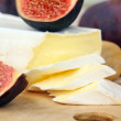 Brie cheese and sweet fruit  figs on a wooden board - Stock Photo