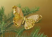 Christmas decoration (golden butterfly) on the branches of fir — Stock Photo