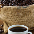 Linen bag of coffee beans and a cup of espresso on a wooden table — Stock Photo #13620961