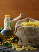 Linen bag of pasta (penne) and a bottle of oil on wooden table — Stock Photo