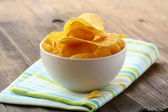 Potato chips in a white bowl on a wooden table — Stock Photo