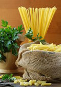 Linen bag of pasta (penne) on a wooden table — Stock Photo
