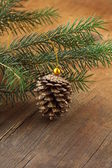 Green fir branches and christmas decorations on a wooden background — Stok fotoğraf
