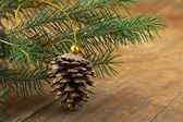 Green fir branches and christmas decorations on a wooden background — ストック写真