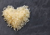 Pile of white rice in heart shape — Stock Photo