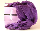 Warm knitted purple scarf in shopping bag — Stock Photo