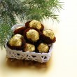 Chocolate truffles in a gift box under the Christmas tree — Stock Photo #14066576