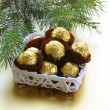 Chocolate truffles in a gift box under the Christmas tree — Stock Photo #14143839