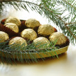 Chocolate truffles in a gift box under the Christmas tree — Stock Photo