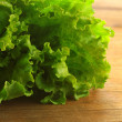 Green lettuce on wooden board — Stock Photo