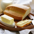 Butter,  loaf of white bread and milk on wooden plate - Stock Photo