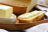Butter, loaf of white bread and milk on wooden plate — Stock Photo
