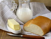 Butter, loaf of white bread and milk — Stock Photo