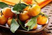 Ripe juicy tangerine, orange mandarin with leaves on wooden table — Stock Photo