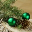 Green fir branches and christmas decorations on a wooden background — Stock Photo #15509299