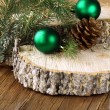 Green fir branches and christmas decorations on a wooden background — Stock Photo