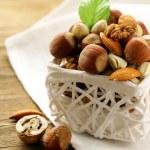 Mix nuts - walnuts, hazelnuts, almonds in a white basket — Stock Photo #15711365