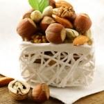 Mix nuts - walnuts, hazelnuts, almonds in a white basket — Stock Photo #15726079