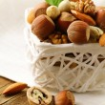 Mix nuts - walnuts, hazelnuts, almonds in a white basket — Stock Photo #15880761
