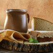 Ceramic jug with milk and a loaf rye black bread, on a wooden table , rustic style — Stock Photo #16017333