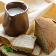 Ceramic jug with milk and a loaf rye black bread, on a wooden table , rustic style — Stock Photo #16017421