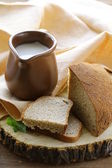 Ceramic jug with milk and a loaf rye black bread, on a wooden table , rustic style — Stock Photo