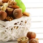 Mix nuts - walnuts, hazelnuts, almonds in a white basket — Stock Photo #16246105