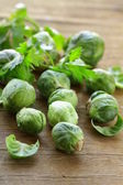 Fresh raw brussels sprouts on a wooden table — Stock Photo