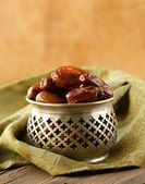 Sweet dates in bowl on a wooden table — Stockfoto