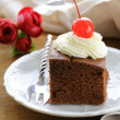 Stock Photo: Chocolate birthday cake with cherries and whipped cream