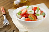 Italian Caprese salad with cherry tomatoes and baby mozzarella — Stock Photo