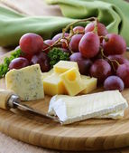 Cheeseboard with three kinds of cheese and grapes — Stock Photo