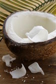 Half a fresh coconut on a wooden table — Stock Photo