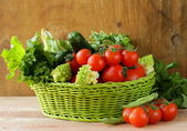 Fresh vegetables (cucumbers, tomatoes, cabbage romanesco and green beans ) and herbs mix in a wicker basket — Stock Photo