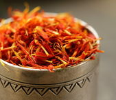 Saffron spice in metal bowl macro shot soft focus — Stock Photo