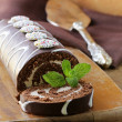 Stock Photo: Chocolate cake roll with vanilla cream on a wooden board