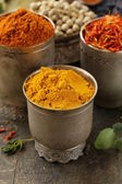Various spices (curcuma, paprika, saffron) in metal bowls — Stock Photo