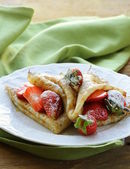 Dessert crepes with strawberries and powdered sugar — Stock Photo