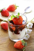 Dairy dessert with chocolate sauce and strawberries — Stock Photo