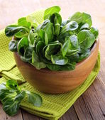 Fresh green salad valerian in a wooden bowl — Stock Photo