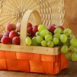Red and green grapes in a wicker basket - Stock Photo