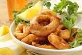Fried squid rings dipped in batter with lemon — Stock Photo