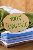 Stack of multicolored clothing with organic label — Stock Photo
