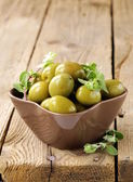 Green marinated olives with oregano on a wooden background — Stockfoto
