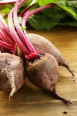 Fresh organic beets with leaves on a wooden background — Foto de Stock