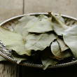 Dried bay leaves on a silver plate — Stock Photo