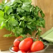 Fresh wet cherry tomatoes and bunch of parsley on the table — Stock Photo