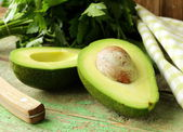 Ripe avocado cut in half on a wooden table — Stock Photo