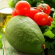 Still life of fresh vegetables (avocado, tomato) olive oil and herbs — Stock Photo #25684857