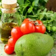 Still life of fresh vegetables (avocado, tomato) olive oil and herbs — Stock Photo #25684897